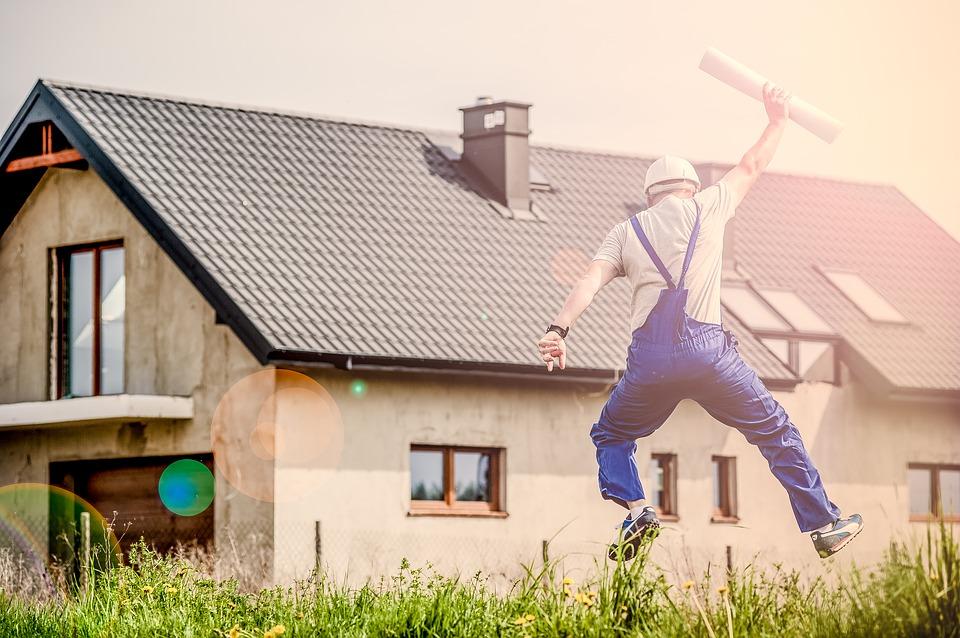 Byggemand springer af glæde foran bolig
